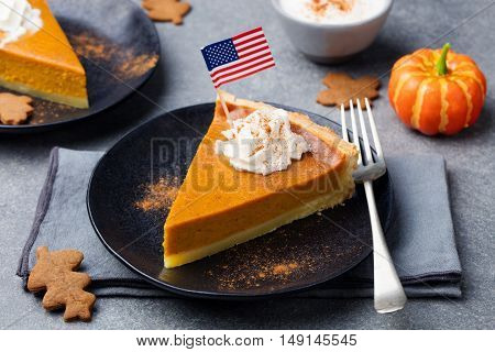 Pumpkin pie, tart made for Thanksgiving day with whipped cream on a black plate with American flag on top. Grey stone background.