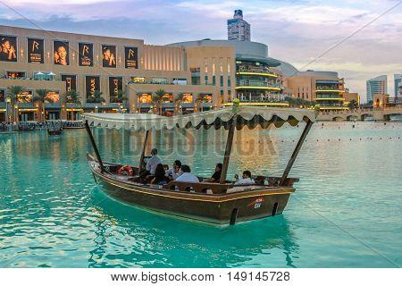 Dubai, United Arab Emirates - May 1, 2013: wooden boat in lake of Dubai fountain show area near Dubai Mall and Burj Khalifa. On the background, the Souk Al Bahar at twilight.