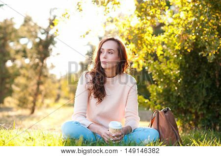 Beautiful giel 20-24 year old resting in park drinking coffee sitting on green grass outdoors. Looking away. Wearing casual clothes: knitted sweater and denim pants.