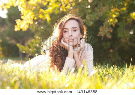 Beautiful girl 20-25 year old lying on green grass in park in sunny day. Looking at camera.