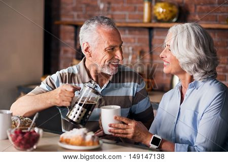 Coffee-break. Elderly partners having desserts at the kitchen of their family house