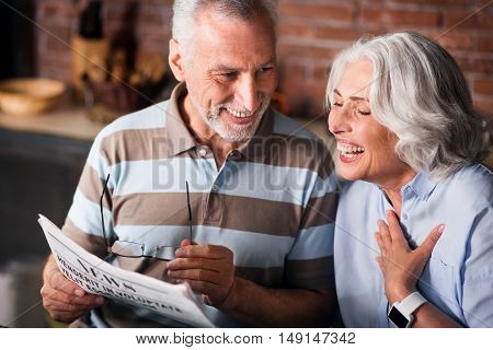 Funny. Attractive old couple having fun while reading morning newspaper