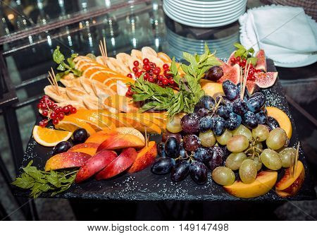 Fresh ripe fruits, berries and mint arrangement on a black stone tray. Sliced peach, orange, banana, fig, grape and viburnum clusters, decorated by mint and sugar powder