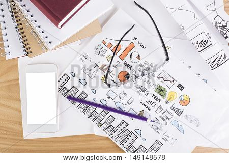 Top view of messy office desktop with blank white smartphone business sketches spiral notepads closed hardcover book and glasses. Mock up