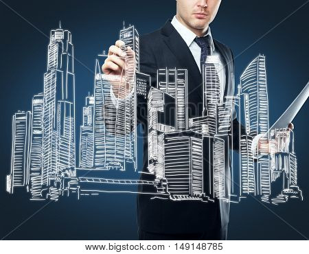Businessperson with document in hand drawing creative city sketch on dark blue background