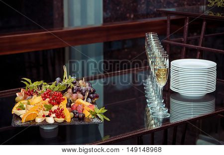 Fresh ripe fruits, berries and mint arrangement on a black stone tray and drinks - white wine, served on glass table, event, catering