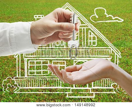 Businessman handing key to female on grass background with creative house sketch. Real estate and mortgage concept