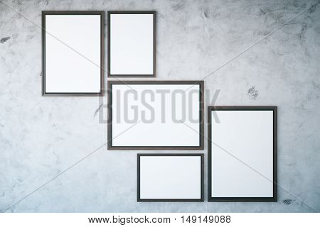 Several picture frames hanging on textured concrete wall. Mock up 3D Rendering