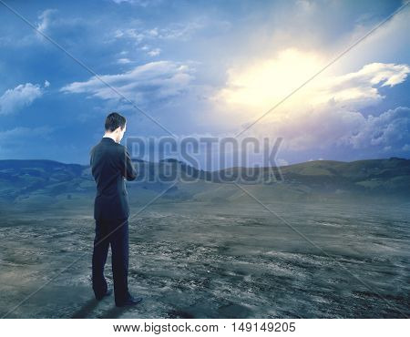 Pensive young businessman in suit standing on landscape background with sunlight. Research concept