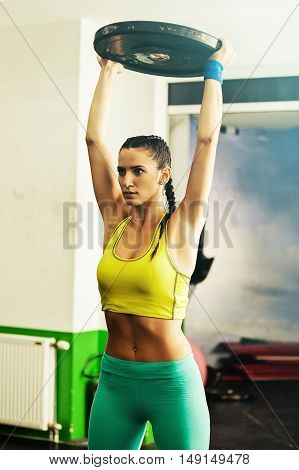 Young fit woman pulling up weight. Cross fit training.