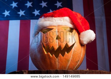 Jack-o '- lantern in a red Santa hat on American flag background, happy holidays, Jack-o ' - lantern-patriot