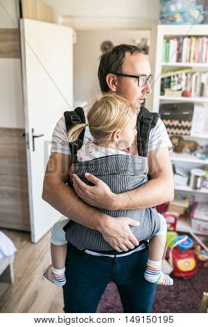 Young father with his daughter in baby carrier at home