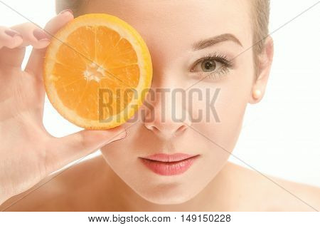 Beautiful young seminude woman of European appearance holds an orange in front of her eyes standing on white background