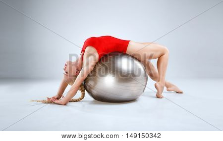 Slim female fitness model is posing in a white studio