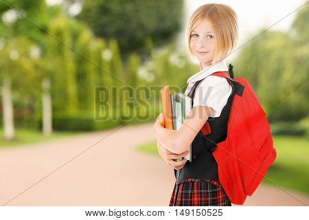 Cute girl with backpack and books on blurred nature background. School concept.