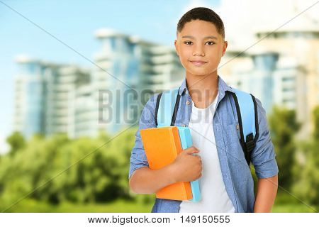 Cute boy with backpack and book on blurred city background. School concept.