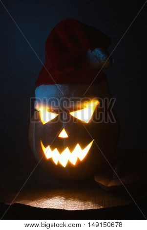Jack-o ' - lantern scary shining eyes in the darkness. Pumpkin in the hat of Santa. The Eve Of Halloween
