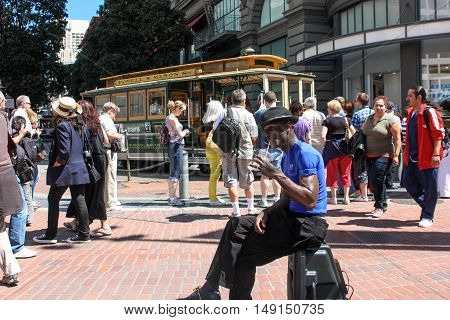San Francisco, California, United States - 11 June 2010. Street musician and dancer sat on his electroacoustics relax and have a drink. People around are busy with their chores. Someone is waiting for the tram, some make photos, someone just walking.