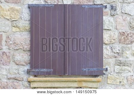 Wooden closed window on a stone wall.