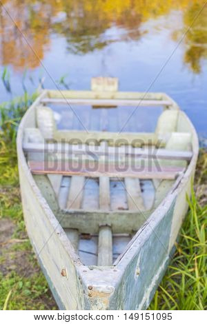 blurred background landscape submerged old boat in grass on the bank of river in autumn