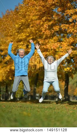 Happy fit senior couple jumping in autumn park