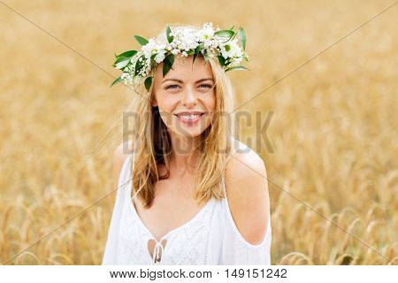 happiness, nature, summer holidays, vacation and people concept - smiling young woman in wreath of flowers on cereal field