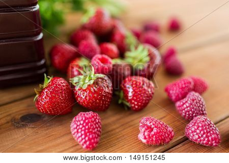 healthy eating, food, dieting and vegetarian concept - bottle with juice and berries on wooden table