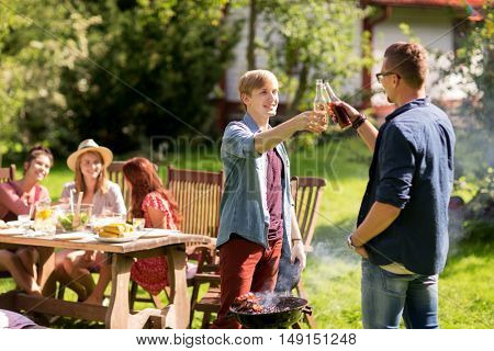 leisure, food, people, friendship and holidays concept - happy friends cooking meat on barbecue grill and drinking beer at summer outdoor party