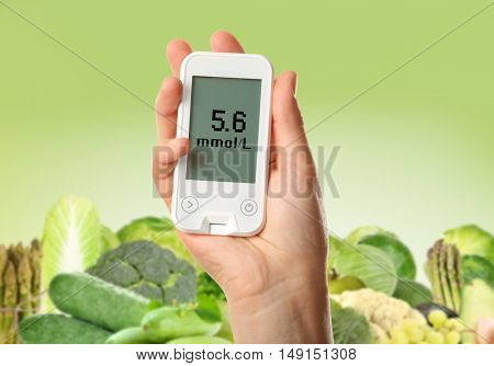 Male hand holding glucometer with vegetables and fruits on green background. Diabetes concept