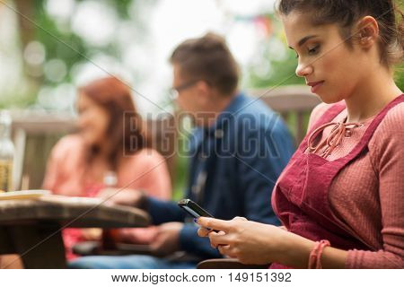 leisure, holidays, people and technology concept - close up of young woman or teenage girl texting on smartphone and friends having dinner at summer garden party