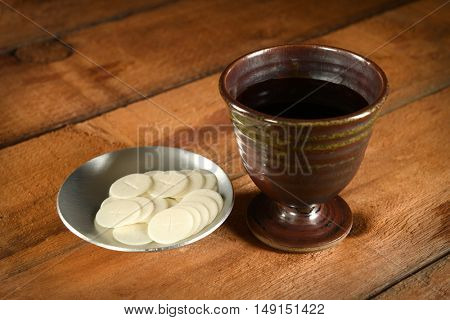 Communion wafers and cup of wine on wooden table