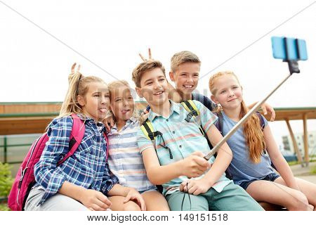 primary education, technology, friendship, childhood and people concept - group of happy school students with backpacks sitting on bench and taking picture by smartphone on selfie stick outdoors