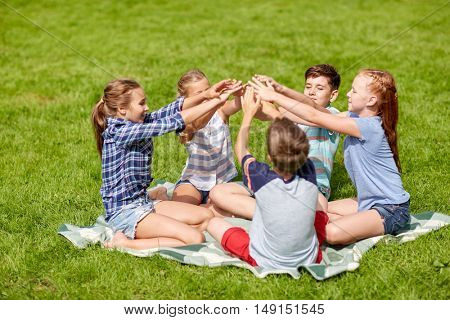 summer holidays, friendship, childhood, leisure and people concept - group of happy pre-teen kids putting hands together in park