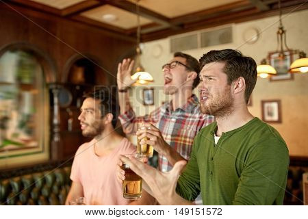 people, men, leisure, friendship and celebration concept - male friends or fans watching sport game or football match at bar or pub