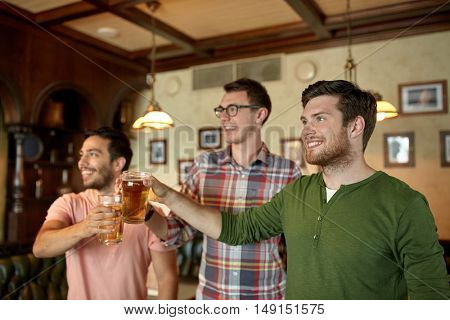 people, men, leisure, friendship and celebration concept - happy male friends clinking beer glasses and watching sport game or football match at bar or pub