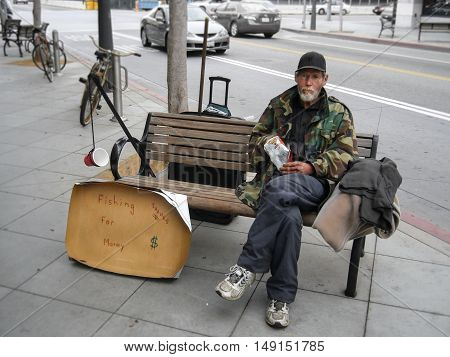 Los Angeles, CA, United States - 16 June 2010. Unemployed man sitting on a bench and begging for money. Very witty writing on the carton reads: he catches fish - money.