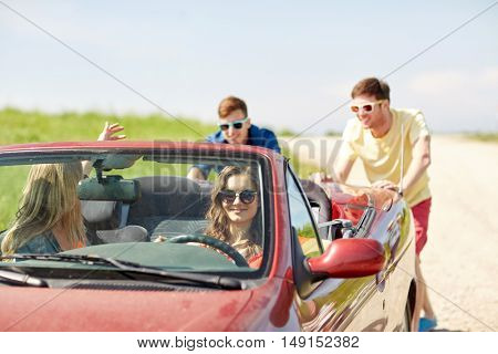 leisure, road trip, travel and people concept - happy friends pushing broken cabriolet car along country road