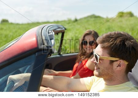 leisure, road trip, travel, summer holidays and people concept - happy couple driving in cabriolet car at country