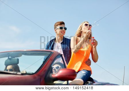 leisure, road trip, travel and people concept - happy friends driving in cabriolet car along country road and blowing bubbles