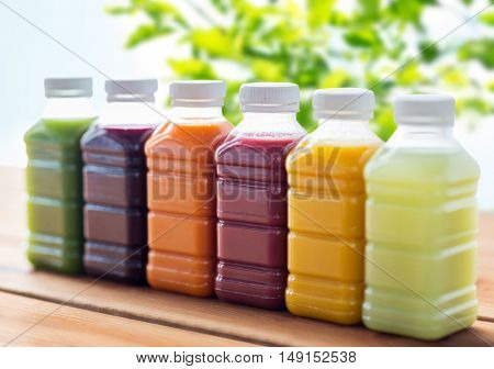 healthy eating, drinks, dieting and packaging concept - plastic bottles with different fruit or vegetable juices on wooden table over green natural background