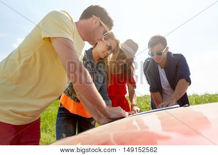 leisure, road trip, travel and people concept - happy friends with map and car searching location at country