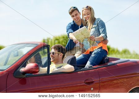 leisure, road trip, travel and people concept - happy friends with map driving in cabriolet car along country road and searching location
