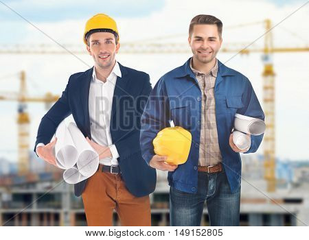 Professional engineers with blueprint on blurred city background