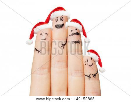 family, holidays, christmas and body parts concept - close up of hand with four fingers in santa hats with smiley faces
