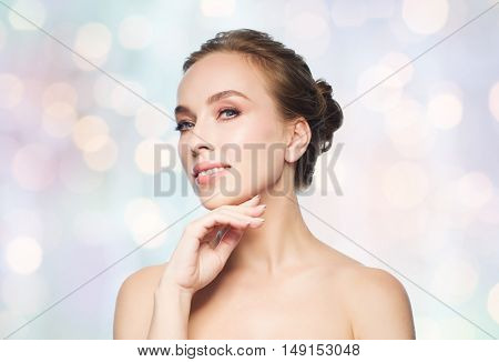 beauty, people and health concept - beautiful young woman touching her face over blue holidays lights background