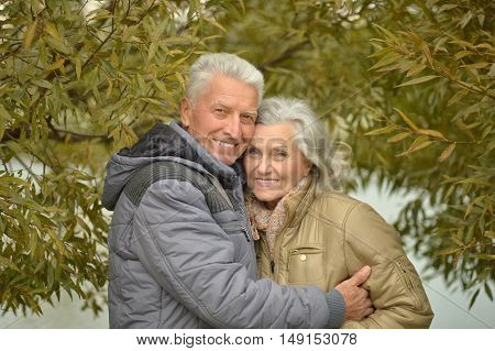 Happy senior couple near water at autumn park