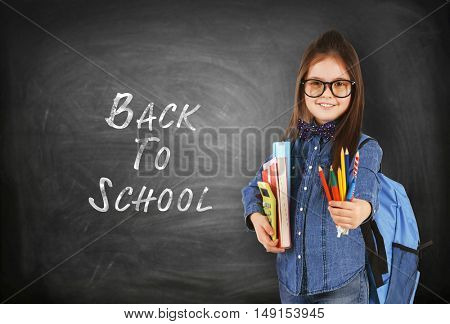 School concept. Cute girl with backpack holding book on blackboard background. Text back to school.
