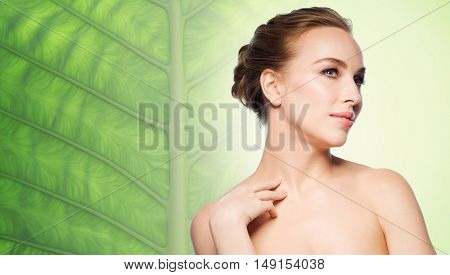 beauty, people, bodycare and health concept - beautiful young woman touching her neck over natural green leaf background