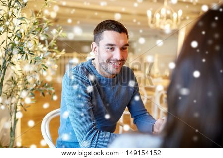 people, communication and dating concept - happy couple talking at cafe or restaurant