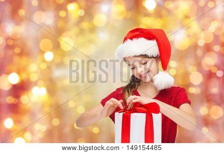 christmas, holidays, winter, children and people concept - smiling girl in santa helper hat with gift box over lights background